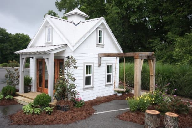 a traditional shed with accordion garage door with glass detail