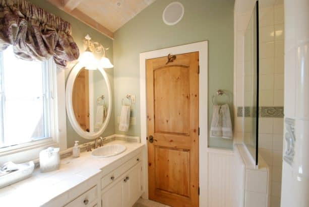 knotty pine wood door paired with white trim to deal with space limitation in a traditional bathroom