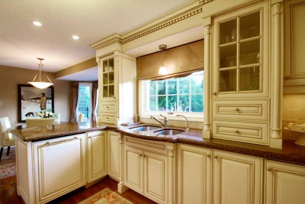 a traditional kitchen looks elegant and luxurious with cream white cabinets, crown molding, and brown granite countertops