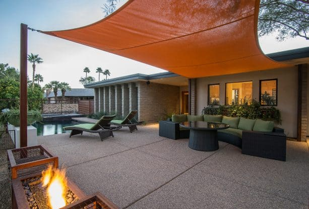 an exposed aggregate concrete comes with a sun shade sail for extra comfort