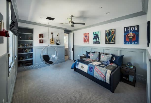 a transitional kid's bedroom with white walls, grey trim, and grey recessed-panel wainscoting