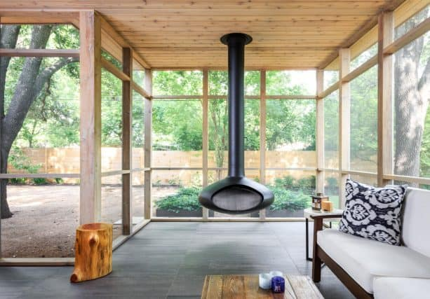 a black hanging fireplace in a modern screened porch