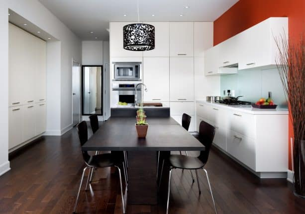 a contemporary kitchen with stunning red accent, white cabinets, and black table set