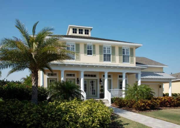 soft yellow, white, and sage green tropical exterior design