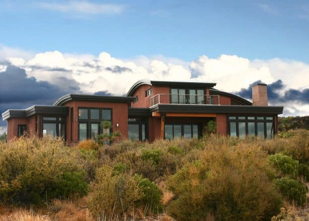 a contemporary exterior with the combination of red stucco and black trim