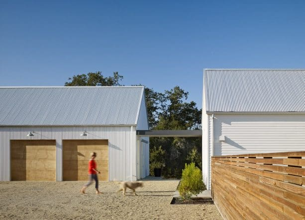 the house and the farmhouse garage is connected with a walkway covered with a roof-extension from the main building