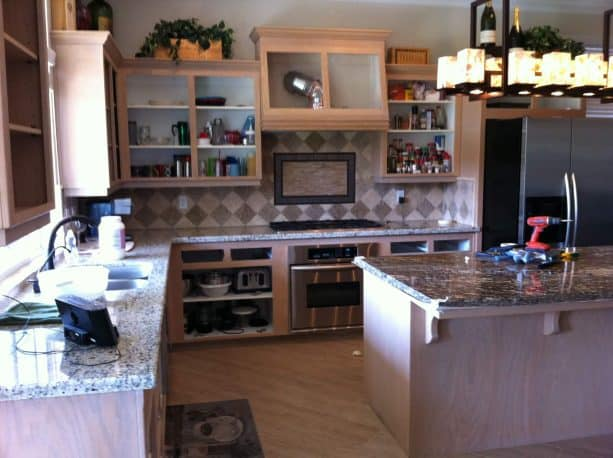 the open white-washed oak cabinets look untidy before the update