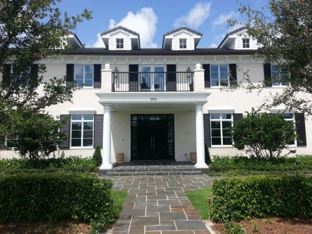 a white traditional house with black shutters and black roof