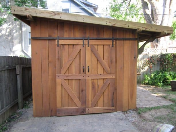 an eclectic wooden garden shed with sliding barn garage door