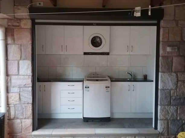 the laundry closet interior with black and white cabinetry theme shown when the rolling door is open