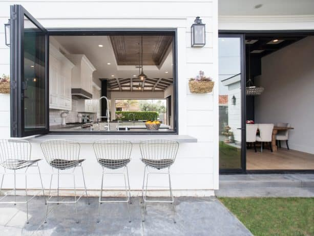 a black bi-fold pass through window looks attractively simple being paired with the white wall siding