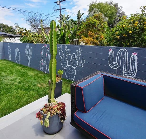 grey painted cinder block barrier walls with white cute cactus murals on it