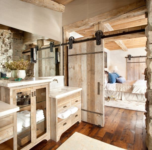 a wooden barn door with stunning wheels and hangers in a rustic interior