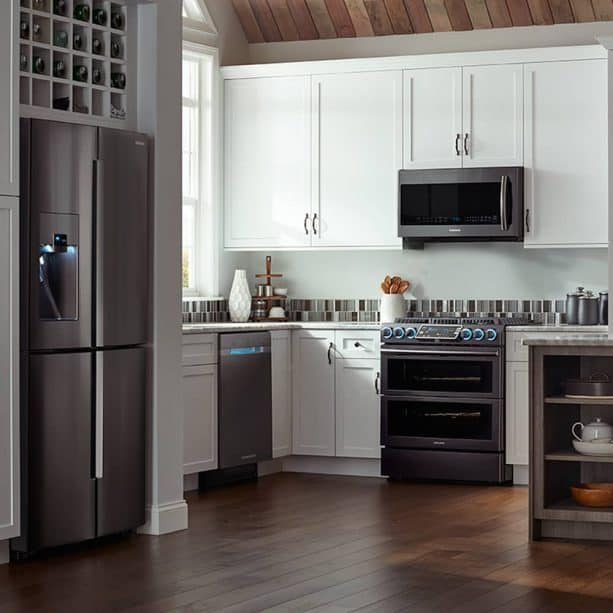 a white contemporary kitchen with complete slate appliances and white cabinets
