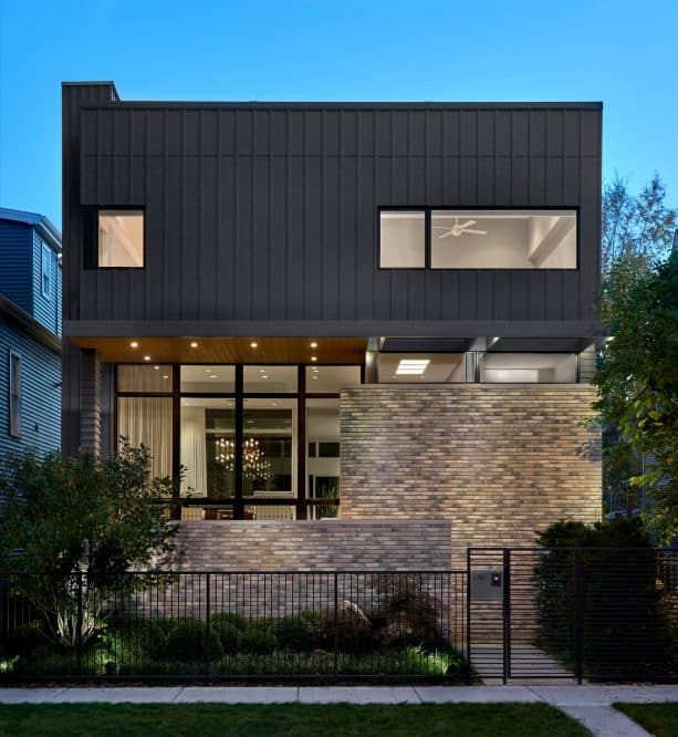 an industrial contemporary living place with half mixed tan brick and half charcoal grey siding