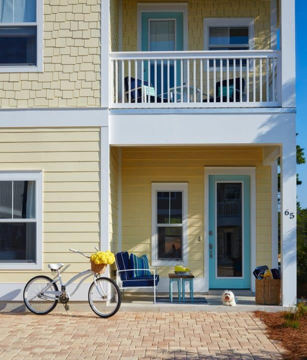 charming exterior with pale yellow, white, and sea glass blue color scheme