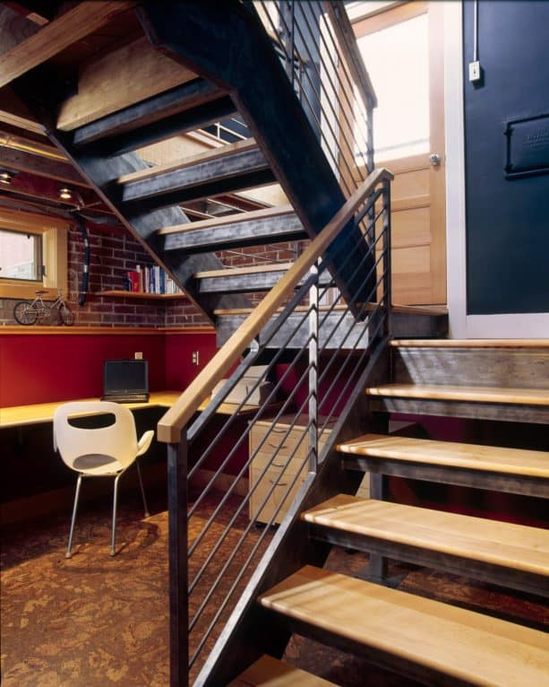 a contemporary no-riser basement staircase with an office under it