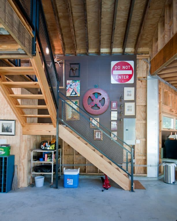 a wooden open staircase with metal rail for an industrial basement