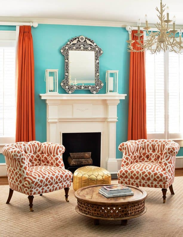 a traditional interior with bright blue walls and orange curtains