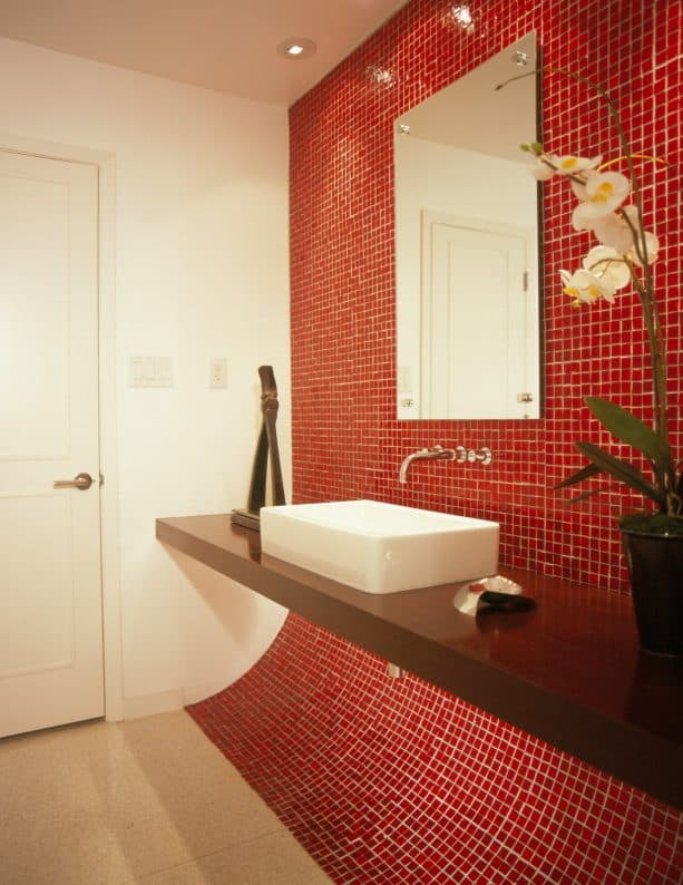 a contemporary bathroom with unique red mosaic glass accent wall and floating black vanity