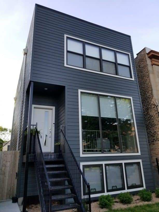 a modern home exterior design with dark grey walls and white trim