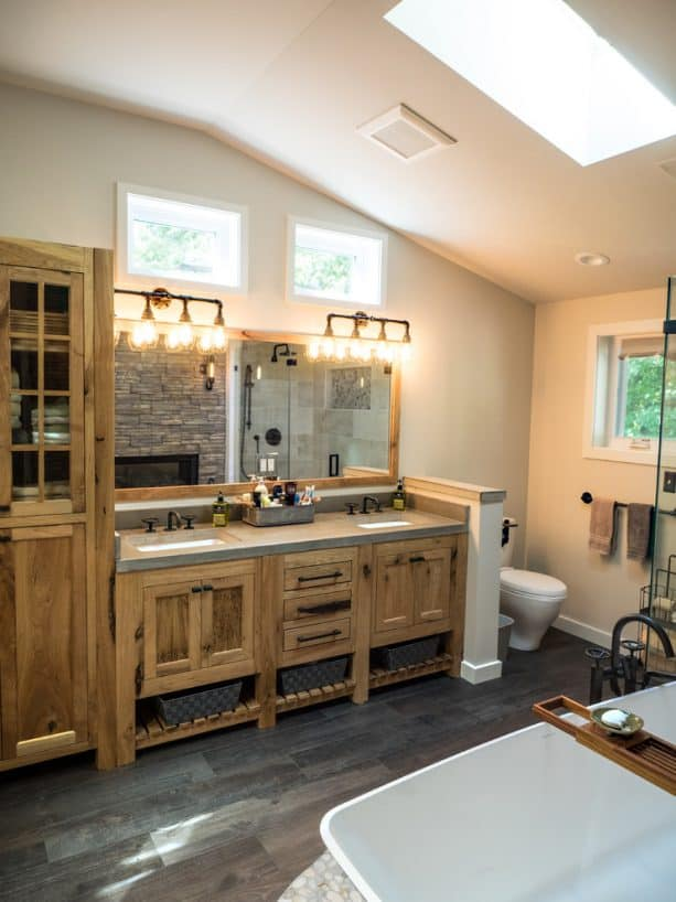 a rustic bathroom with custom hickory cabinets and unique dark wood floor