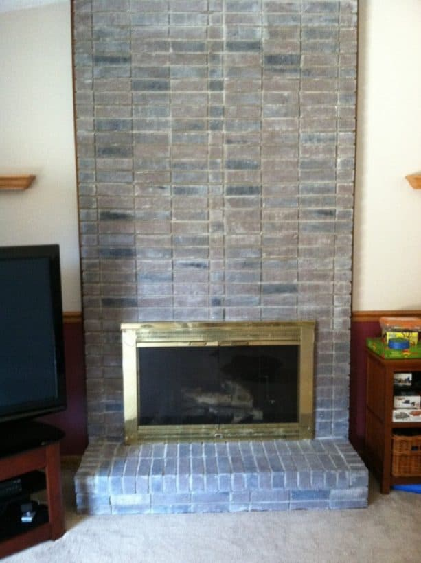 modern fireplace with gray color-washed wall-size brick mantel and support
