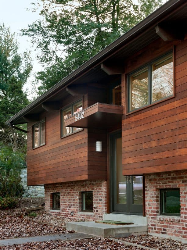 wider wood stained wood siding paired with old orange brick in a contemporary home exterior