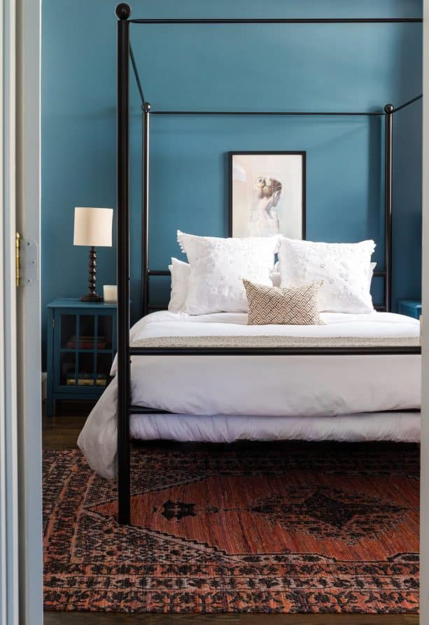 a black traditional canopy bed in a teal transitional bedroom design
