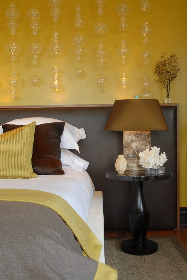 grey and yellow room with oversized leather headboard