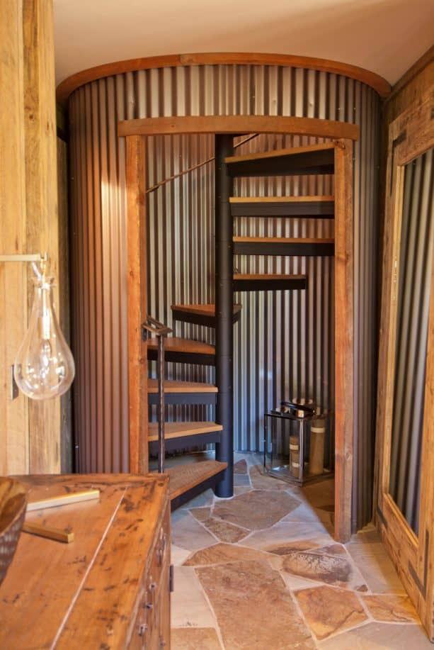 a spiral open staircase with corrugated metal surround in a rustic basement