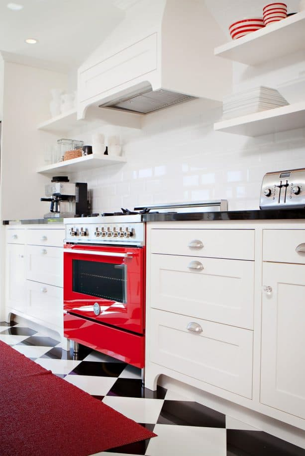 a dominant white color in a traditional kitchen with red range and black countertops