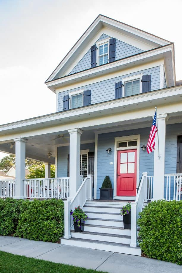 a blue house with a red door and an American flag for a patriotic feel in the home exterior design
