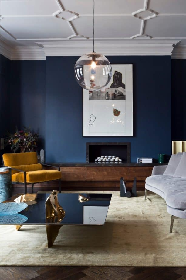 a living room with navy blue wall and wood fireplace hearth