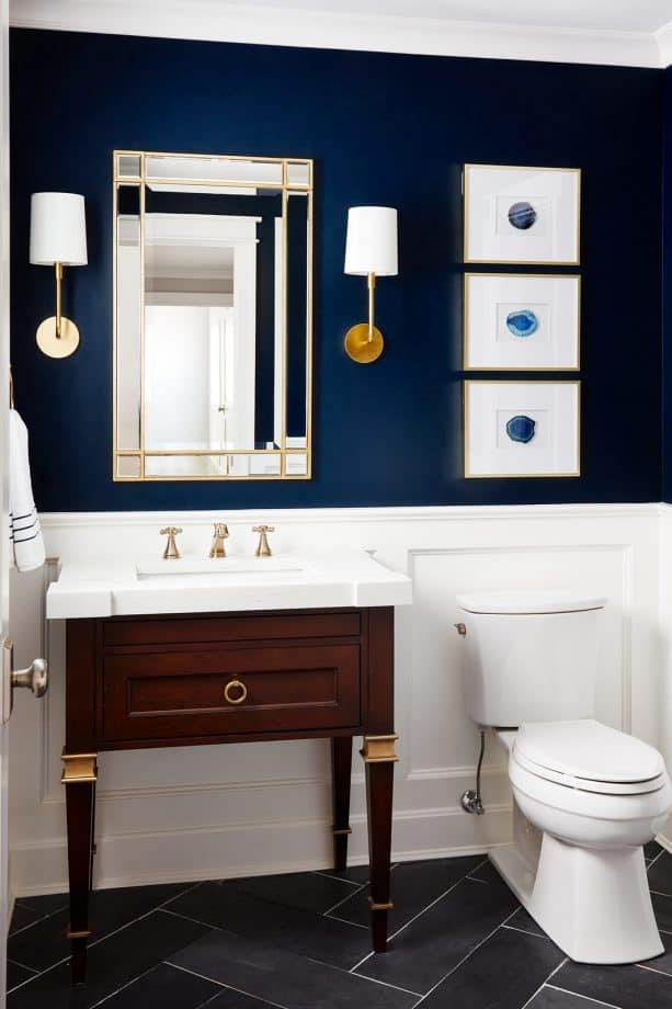 a powder room with navy blue walls and gold accents