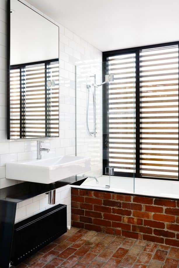 the combination of red brick material and black color in a contemporary bathroom