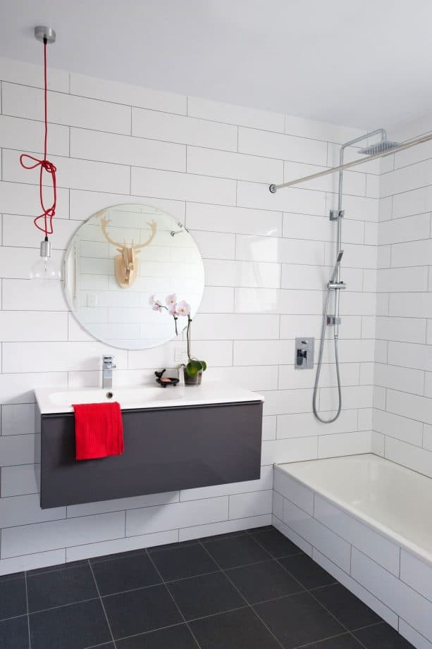 a contemporary bathroom with oversize white subway tile and charcoal gray grout on the wall design