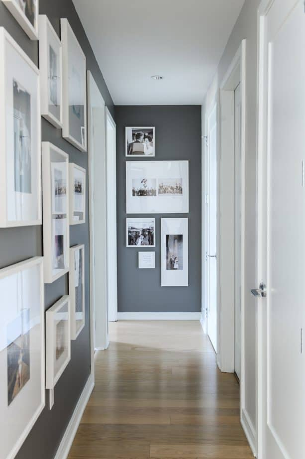 a hallway with dark grey paint and white trim
