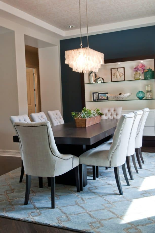 dining room with a navy blue-white accent wall and off-white chairs