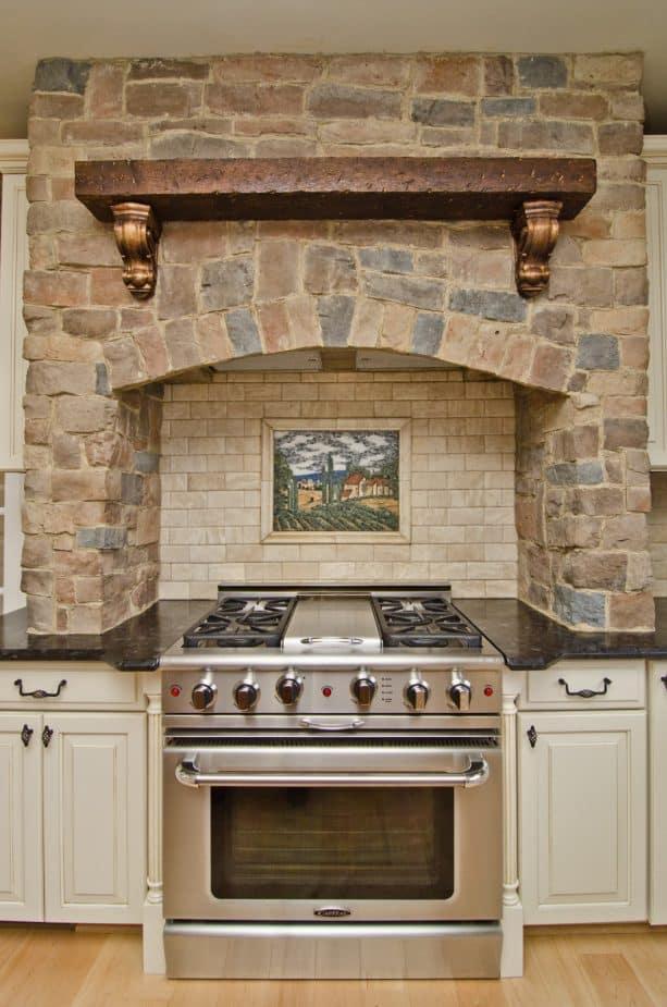 the stunning combination between white cabinets, brown granite countertops, and custom stone brick range hood