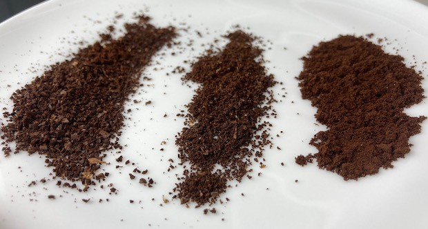 Plate with three piles of coffee grounds in different size particles