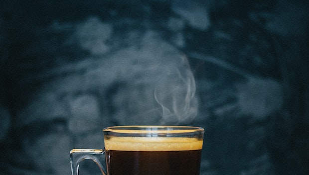 A piping hot cup of Nespresso coffee with steam rising from the top