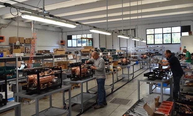 Technicians on a factory floor build espresso machines