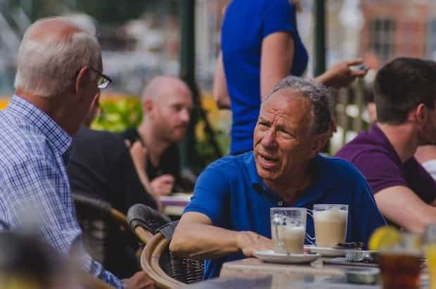 Two gentlemen have an animated discussion over caffe lattes outside an Amsterdam coffee shop