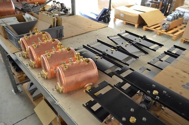 Copper boilers spread out on a table at an espresso machine factory
