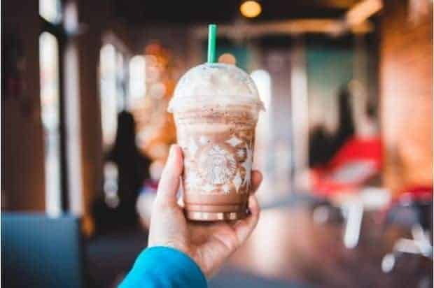Hand holding up a chocolatey whipped coffee drink inside a Starbucks coffee shop