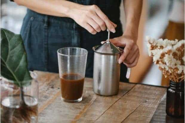 Barista pumping the plunger on a stainless steel French press to make cold foam
