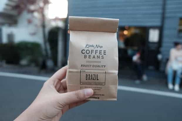 A hand holding up a brown paper bag of Brazilian coffee beans