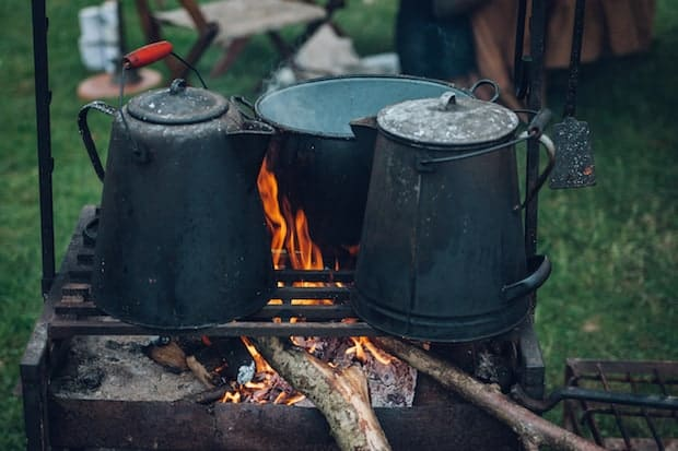 Battered tin coffee pots blackened by carbon over an open fire