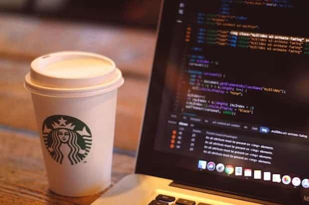 Tall Starbucks cup next to a Macbook computer
